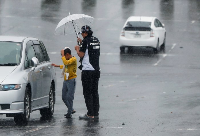 A family member of a Formula One fan gets into a car at a makeshift evacuation center for spectators of Formula One Japanese Grand Prix at Suzuka Circuit in Suzuka, central Japan. (Reuters Photo)