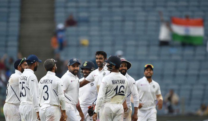 Indian cricket players stand in huddle as they celebrate after the wicket of South Africa's batsman Keshav Maharaj during the third day of play of the second test cricket match between India and South Africa, at the Maharashtra Cricket Association Stadium in Pune on October 12, 2019. (Photo by PUNIT PARANJPE / AFP)