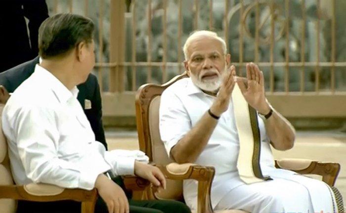 Prime Minister Narendra Modi speaks with Chinese President Xi Jinping, in Mamallapuram. (PTI Photo)