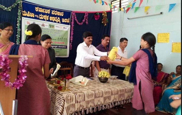 Deputy Commissioner G Jagadeesha hands over a gift to a student at National Girls' Day celebrations organised at State Home in Udupi.