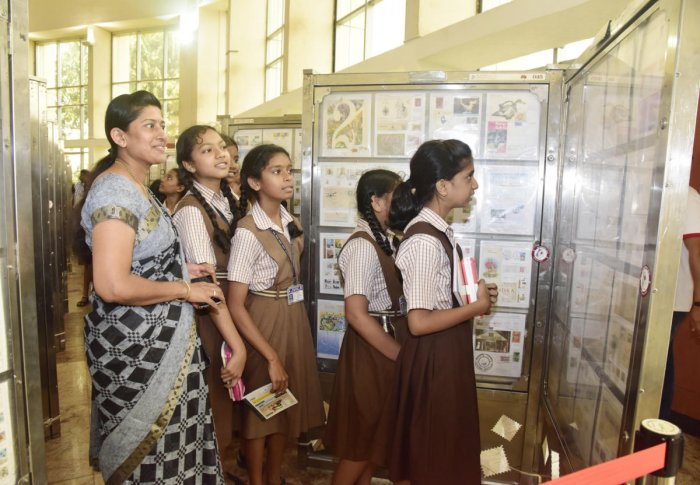 Schoolchildren view the stamps exhibition at 'Karnapex 2019' at TMA Pai Convention Hall in Mangaluru.