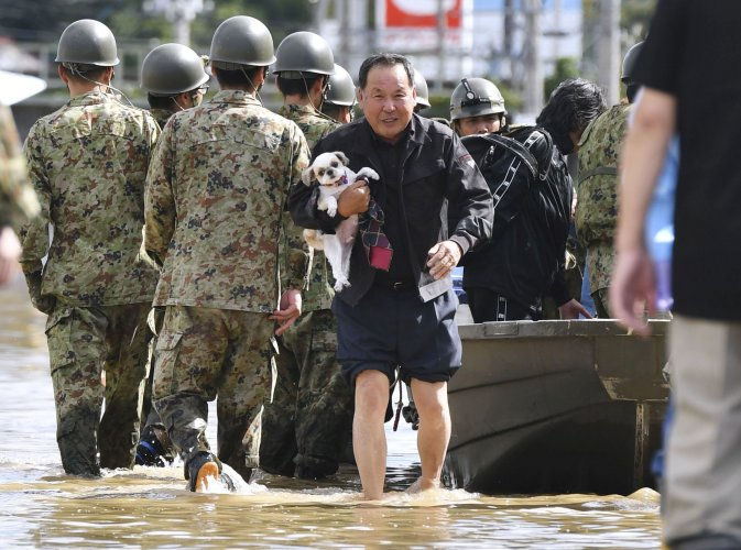 A local resident carrying his pet dog evacuates from an area flooded by the Abukuma river, caused by Typhoon Hagibis, in Motomiya, Fukushima prefecture, Japan. (Reuters Photo)