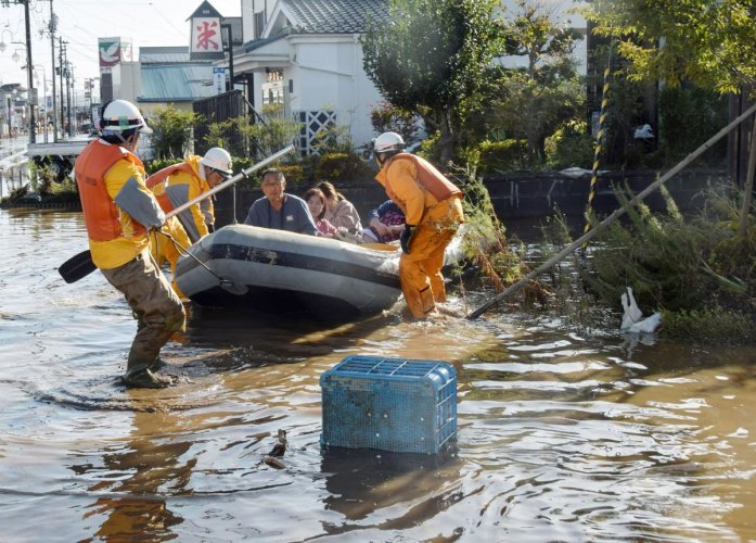 Fire department workers evacuate residents from a flooded area in Date, Fukushima prefecture on October 13, 2019, one day after Typhoon Hagibis swept through central and eastern Japan. AFP Photo