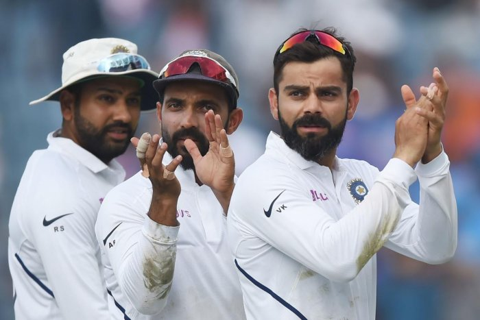 Indian team captain Virat Kohli (R), Ajinkya Rahane (C) and Rohit Sharma gesture towards fans as they celebrate on the fourth day of play after winning the second Test cricket match against South Africa, at the Maharashtra Cricket Association Stadium in Pune on October 13, 2019. (Photo by PUNIT PARANJPE / AFP)