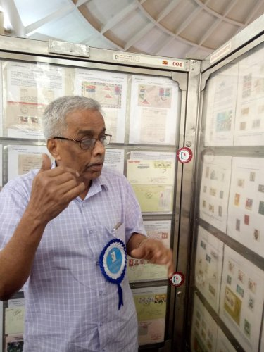 M K Krishnayya explains stamps on the history of flags at Karnapex 2019, at TMA Pai Convention Hall in Mangaluru.