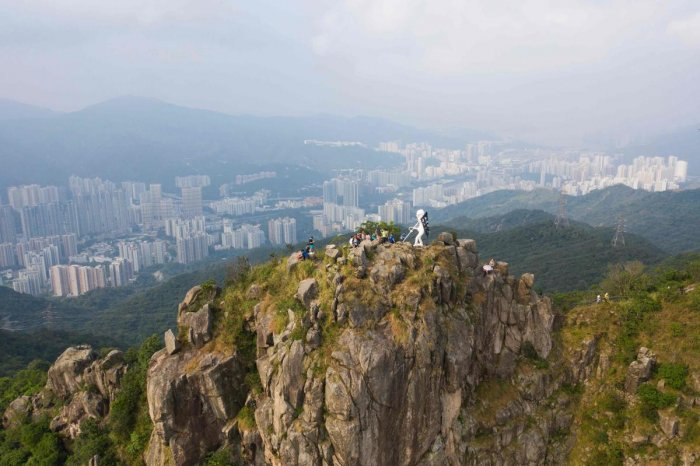 """This aerial photo shows a four-metre statue known as """"Lady Liberty"""" (C), after it was hauled by pro-democracy protesters to the top of Lion Rock, one of the Hong Kong's most famous mountain tops, on October 13, 2019, announcing that the peak would be its"""