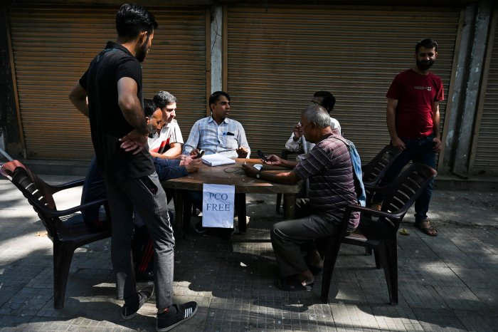 People gather to make calls at a makeshift phone booth set up by Indian security forces outside a camp during a lockdown in Srinagar. (AFP Photo)