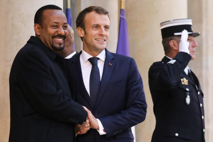 French President Emmanuel Macron (R) shakes hands with Ethiopian Prime Minister Abiy Ahmed. AFP