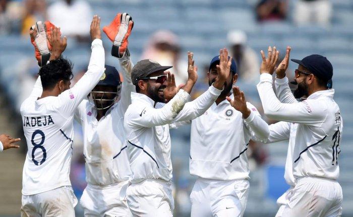 India's deputy Ajinkya Rahane (centre) celebrates with captain Virat Kohli (right) after taking a catch to dismiss South Africa batsman Temba Bavuma on the fourth day of the second Test in Pune on Sunday. AFP