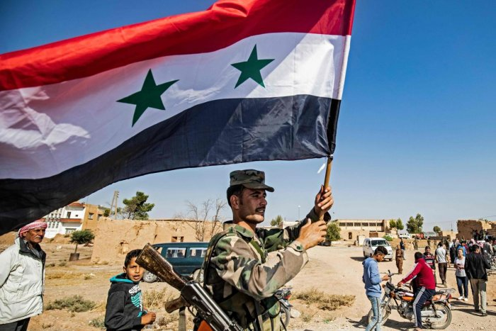 A Syrian regime soldier waves the national flag a street on the western entrance of the town of Tal Tamr in the countryside of Syria's northeastern Hasakeh province on October 14, 2019.(AFP)