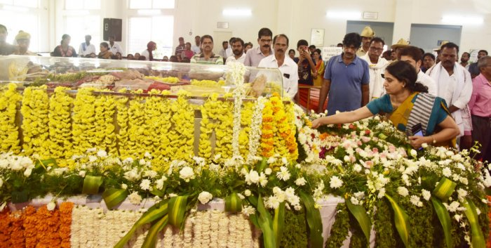 Deputy Commissioner Sindhu B Rupesh places a wreath on the mortal remains of saxophonist Kadri Gopalnath, before the last rites in Mangaluru on Monday. DH photo
