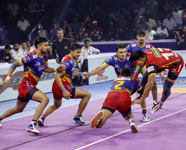 Bengaluru Bulls' Pawan Sehrawat (right) jumps past the UP Yoddha players for a successful raid during the Eliminator 1 in Ahmedabad on Monday.