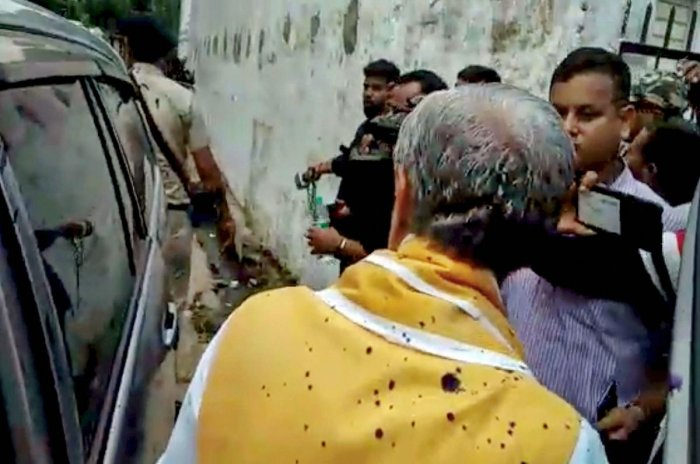 Union Minister of State for Health & Family Welfare Ashwini Choubey, back to camera, after a man threw ink on him while he was visiting dengue patients at Patna Medical College & Hospital, in Patna, Tuesday, Oct. 15, 2019. (PTI Photo)