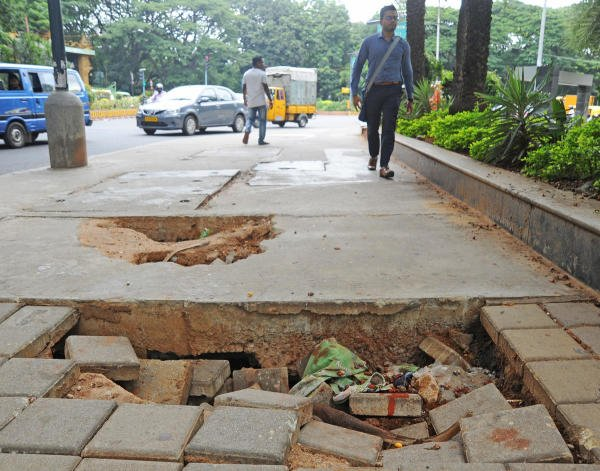 Pedestrians walk near a bad footpath on the TenderSure Vittal Mallya Road in Bengaluru on Tuesday. (DH Photo: Pushkar V)