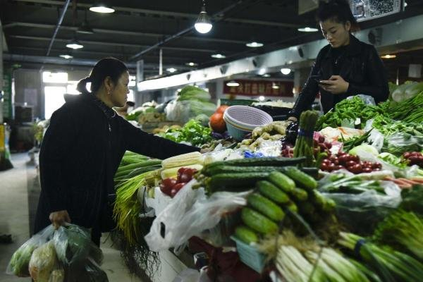 A customer (L) shops for vegetables at a market in Beijing on October 15, 2019. (AFP photo)