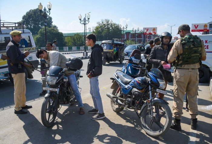 Security personnel check documents of of motorcyclists at a road, during a shut down in Srinagar. (PTI Photo)