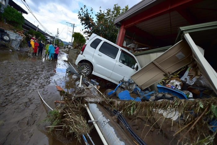 A car sits next to a badly damaged home in Nagano on October 15, 2019, after Typhoon Hagibis hit Japan on October 12 unleashing high winds, torrential rain and triggered landslides and catastrophic flooding. (AFP)