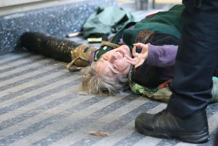 An activist from the Extinction Rebellion climate action movement lies on the floor locked on to the entrance of the building housing the government's Department for Transport in central London on October 15, 2019 as part of Extinction Rebellion's Autumn