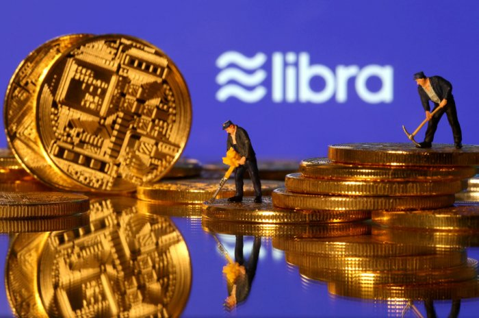 Small toy figures are seen on representations of virtual currency in front of the Libra logo in this illustration picture, June 21, 2019. (Photo by Reuters)