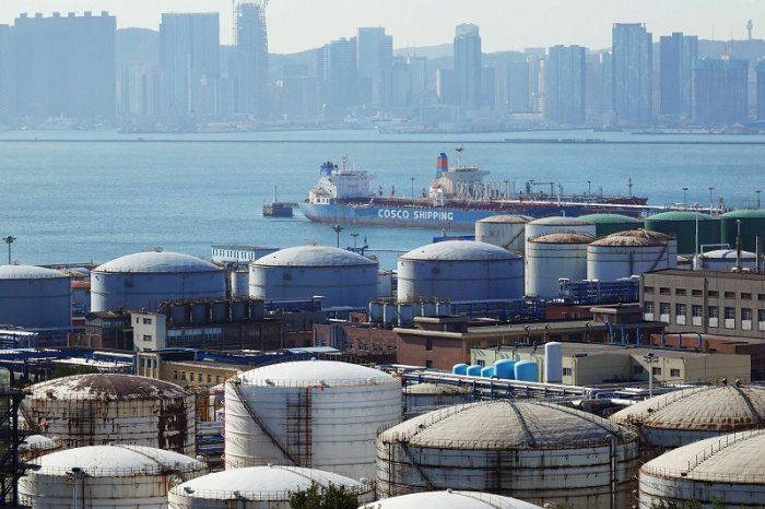 A China Ocean Shipping Company (COSCO) vessel is seen near oil tanks at the China National Petroleum Corporation (CNPC)'s Dalian Petrochemical Corp in Dalian, Liaoning province, China. (Reuters Photo)