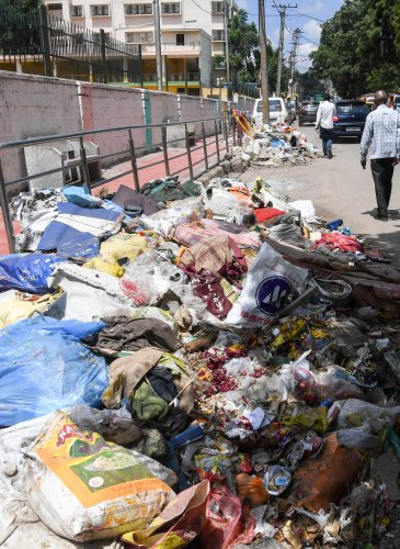 Unclear garbage, which cover the road, in front of Dr.B.R. Ambedkar of Law College, at Srirampura 5th Main road, in Bengaluru on Monday. (DH Photo/ B H Shivakumar)