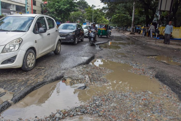 The potholes are getting deeper and bigger on this arterial road, near the KSRTC head office and Shantinagar bus terminal. Thousands of vehicles use this stretch, and no one is doing a thing about the hazards. DH photos by S K Dinesh and Pushkar