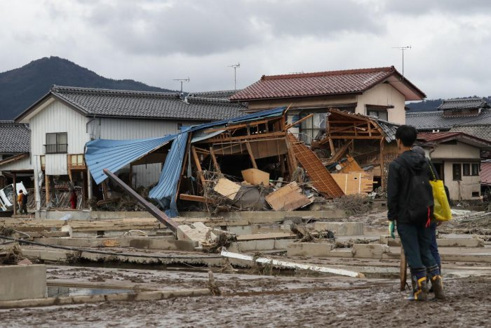 A man looks at flood-damaged homes in Nagano after Typhoon Hagibis hit Japan on October 12 unleashing high winds, torrential rain and triggered landslides and catastrophic flooding. (Photo by AFP)