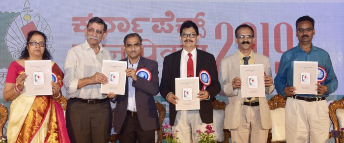 Mangalore University Vice Chancellor Prof P S Yadapadithaya (third from right) and others release the souvenir at Karnapex 2019, the state-level philately exhibition, organised at the Dr T M A Pai Convention Hall on Tuesday.