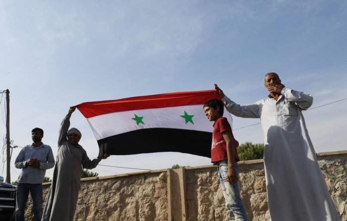 Locals hold the Syrian national flag in the village of al-Sultaniyah on the outskirts of the town of Manbij, which is now controlled by Syrian regime forces. (Photo by AFP)