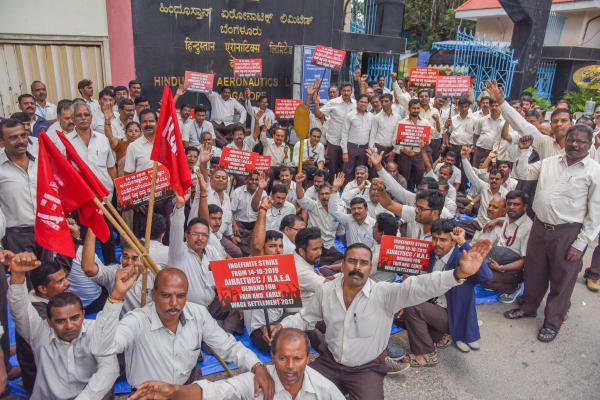 Hindustan Aeronautics Limited (HAL) Employees staging indefinite strike, demanding for fair and early wage revision, under the banner of All India HAL Trade Unions Co ordination committee in front of HAL, Old Airport Road, Bengaluru on Monday. (DH Photo/S K Dinesh)