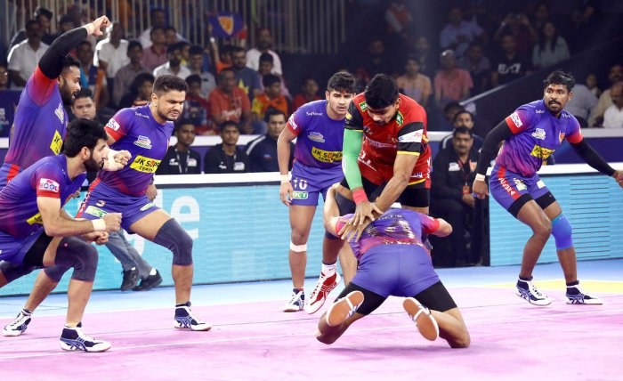Bengaluru Bulls' Pawan Sehrawat (in red) being tackled by Dabang Delhi KC's player in the semifinal of the Pro Kabaddi League season 7