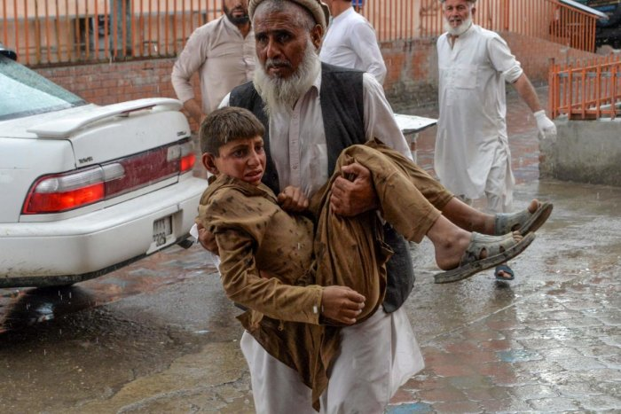 A volunteer carries an injured youth to hospital, following a bomb blast in Haska Mina district of Nangarhar Province on October 18, 2019. AFP Photo
