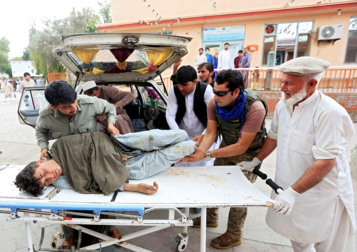 Men carry an injured person to a hospital after a bomb blast at a mosque, in Jalalabad (Reuters Photo)