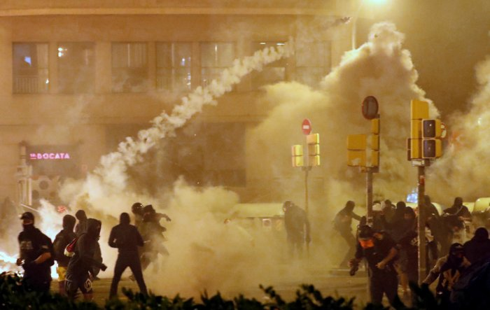 Catalan demonstrators throw back to the police a tear gas canister officer during Catalonia's general strike, in Barcelona, Spain, October 18, 2019. REUTERS/Jon Nazca