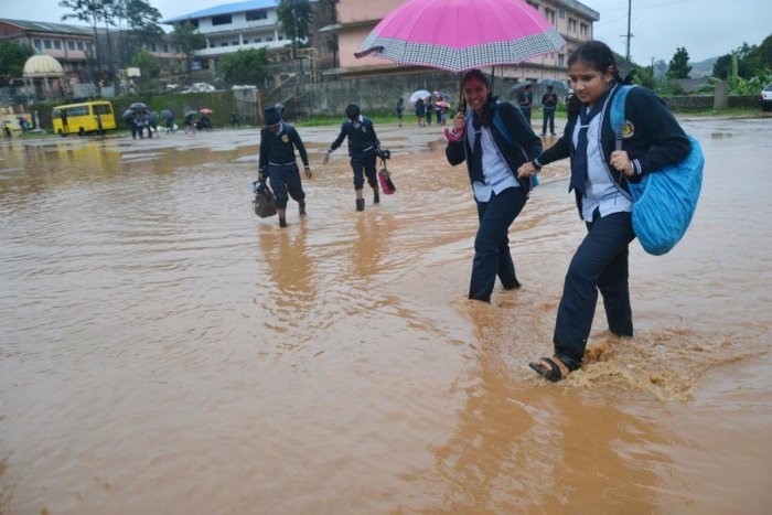Students wade through the inundated Gandhi Maidan in Madikeri on Wednesday. (Right) The Chelyadka bridge on Puttur-Panaje Road in Dakshina Kannada district has been submerged owing to heavy rain. dh PhotoS