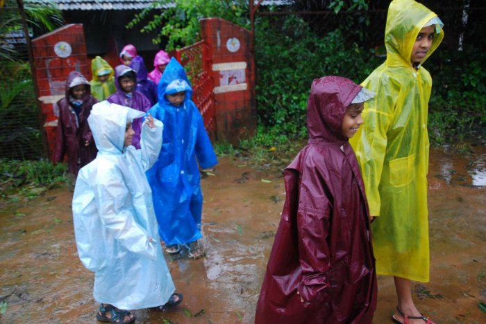 Schoolchildren are on their way back home, with raincoats on, in Madikeri on Tuesday evening.