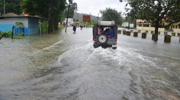 A jeep carries passengers on a flooded road in Bhagamandala. DH Photo
