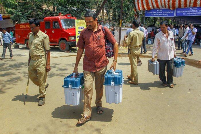 Polling officials leave after collecting EVMs and other election material for the third phase of the 2019 Lok Sabha elections, at a distribution centre, in Bhubaneswar.