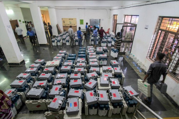 Election staff inspect the boxes containing EVMs and other election material ahead of the third phase of the 2019 Lok Sabha elections, at a distribution centre, in Bhubaneswar. (PTI Photo)