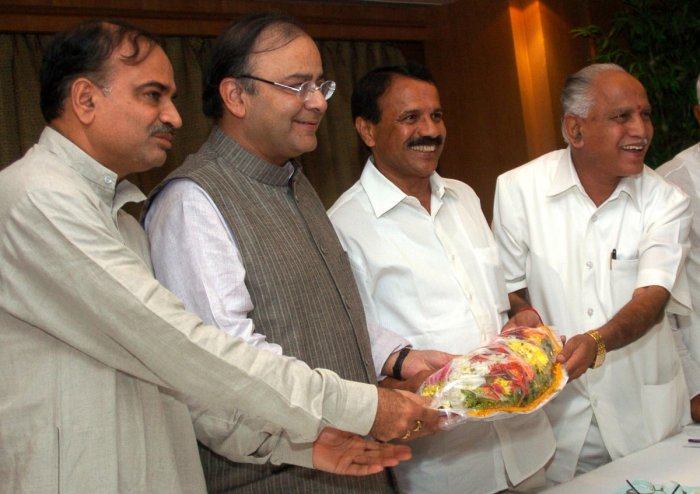Chief Minister B S Yediyurappa hands over a bouquet to former union minister Arun Jaitley at a programme in Bengaluru. BJP leaders Ananth Kumar and D V Sadananda Gowda look on. dh file photo