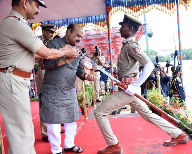 Home Minister Basavaraj Bommai presents the best probationer sword to S Charan in Mysuru. DH Photo