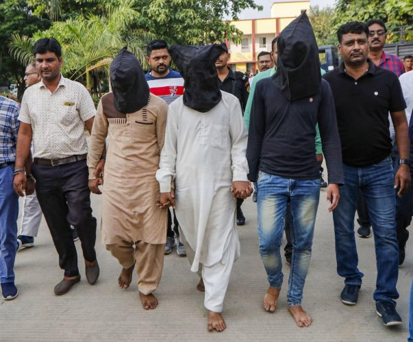Gujarat Anti-terrorist squad (ATS) officers produce and hand over three suspect related to the murder of Hindu Samaj Party founder-leader Kamlesh Tiwari to UP Police, in Ahmedabad, Saturday, Oct. 19, 2019. (PTI Photo)