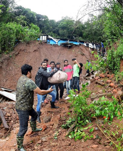 Volunteers shift salvaged articles from a house destroyed by landslides at Mekeri near Madikeri on Monday. DH PHOTO/Krishnakumar P S.