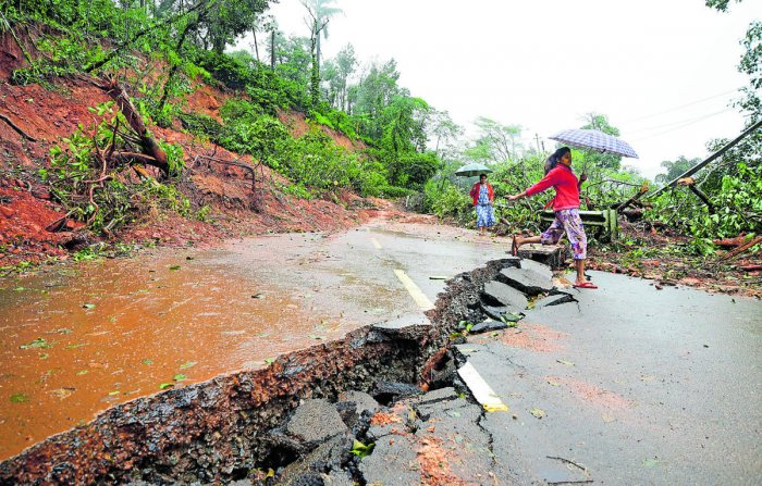 A woman crosses a gaping crack in the Madikeri-Mangaluru road damaged by a landslide. DH Photo