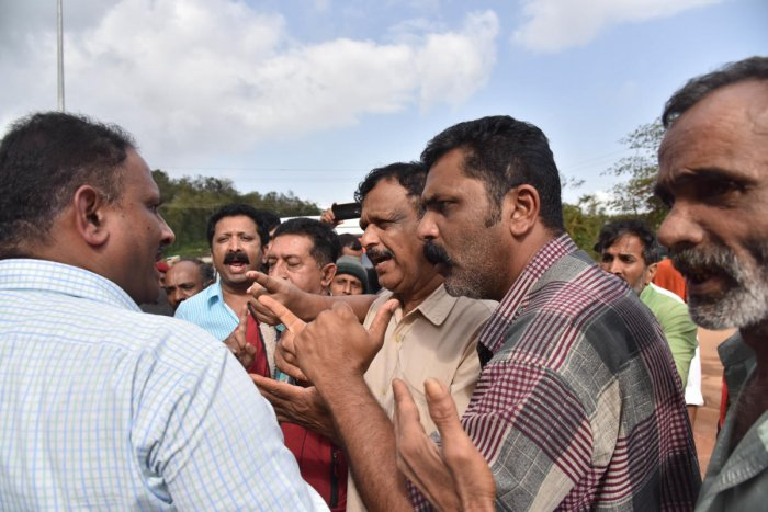 People confront Tahsildar Mahesh (extreme left) at Madapura bus stand in Somwarpet taluk to ensure food supply to rain victims.DH PHOTO / B H Shivakumar