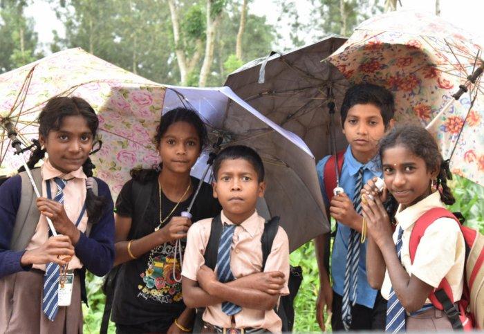 School Children are walking in the rain as few schools started in Madikeri on Thursday. Photo/ B H Shivakumar