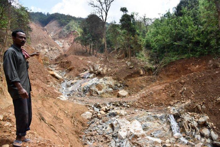 K E Krishnappa Nayaka near his farm after the recent landslides at Second Monnangeri in Kodagu. DH Photo/B H Shivakumar