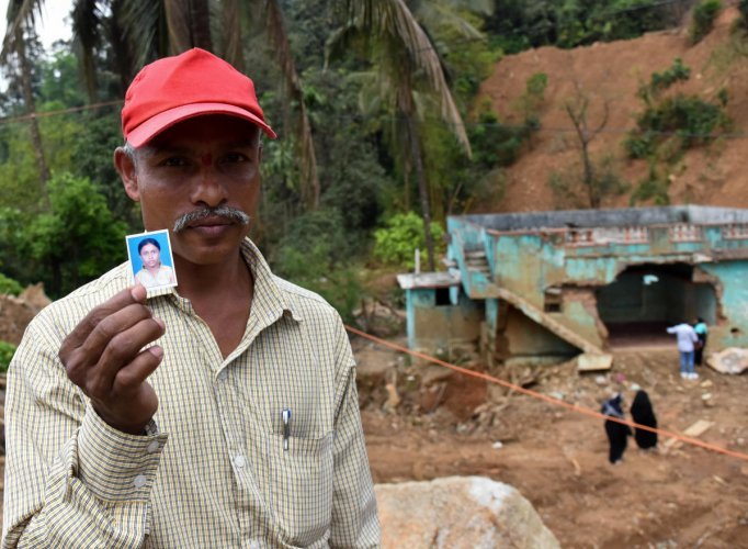 Somaiah shows a photo of his missing daughter Manjula whose body has not yet been recovered after massive landslides destroyed Jodupala village in Kodagu last month. DH Photo/B H Shivakumar