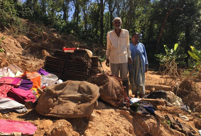 In tatters: Eeshwara and his wife Kaveramma gathered soiled belongings after digging the debris of their house at Emmetalu-Makkandur village in Kodagu district.dh photo/ambarish v
