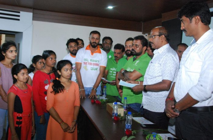 People for People organisation hands over financial assistance to the natural calamity affected students, towards their studies, in Madikeri on Tuesday.